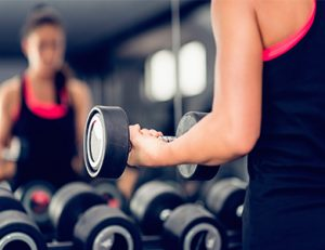 Woman exercising with dumbbell in health club